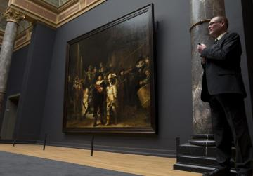 A senior security officer stands next to Rembrandt's The Night Watch painting during a press preview of the renovated Rijkmuseum in Amsterdam Photo:AP