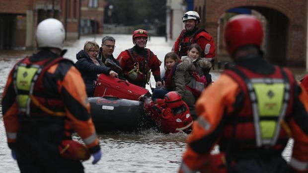 A family is rescued from the centre of York by boat, as swamped towns and cities continue to struggle against the Christmas floods. With more rain forecast for the middle of the week there may be worse to come and the Environment Agency has more severe flood warnings in place - meaning there is still a danger to life. Photo: Owen Humphreys/PA Wire
