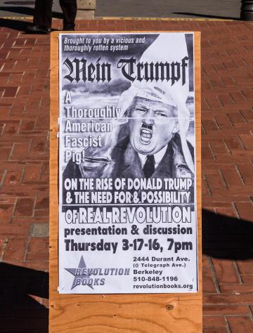 A poster with caricature compares Donald Trump to Adolf Hitler, wearing a hood of the KKK, at the University of California, Berkeley.