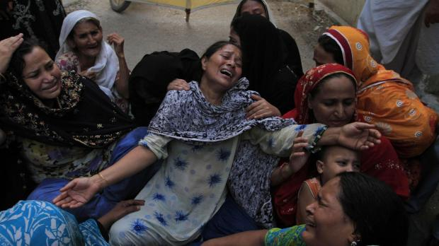 Family members of a target killing victim mourn his death in Karachi. Photo: Shakil Adil