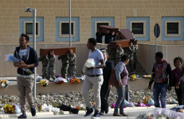 Armed Forces of Malta soldiers carry coffins with the bodies of migrants to an inter-faith burial service as mourning migrants arrive at Mater Dei Hospital in Tal-Qroqq on April 23. European Union leaders who decided last year to halt the rescue of migrants trying to cross the Mediterranean reversed their decision at a summit hastily convened after nearly 2,000 people died at sea. Public outrage over the deaths peaked this week after up to 900 migrants died when their boat sank on its way to Europe from Libya. Photo: Darrin Zammit Lupi