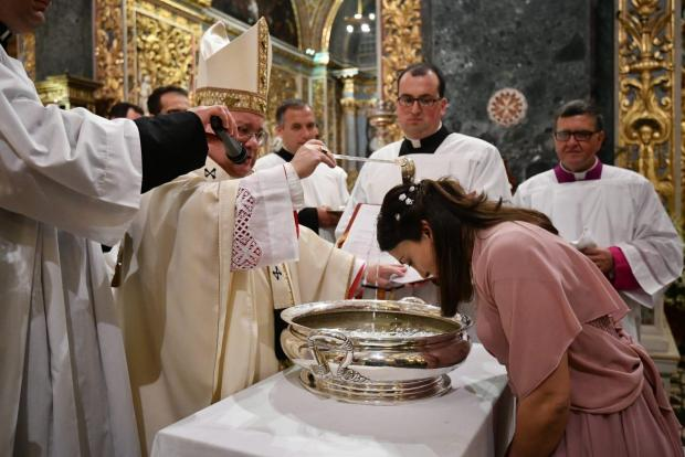 Archbishop Scicluna baptises a new Catholic on Saturday. Photo: Curia