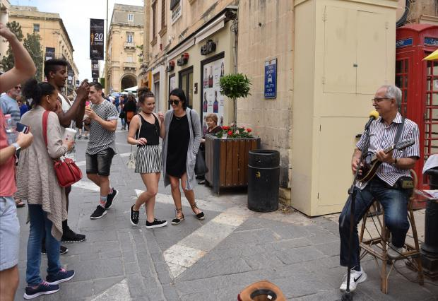 A busker plays the banjo to passersby in Valletta on May 10. Photo: Mark Zammit Cordina
