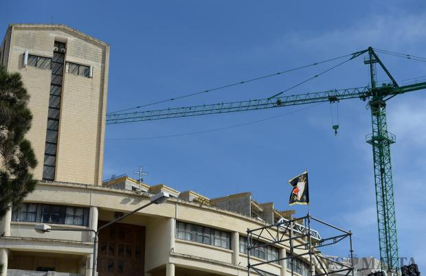 A PN flag flies in the wind as a crane and church are seen in the background. Photo: Matthew Mirabelli