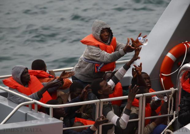 Rescued migrants on the deck of an Armed Forces of Malta (AFM) patrol boat reach out for bottles of water after arriving at the AFM's Maritime Squadron base at Haywharf in Marsamxett Harbour on January 22. A Maltese patrol boat rescued 87 migrants from a floundering drifting dinghy some miles off Mellieha, but another 20 people were feared to have perished. Photo: Darrin Zammit Lupi