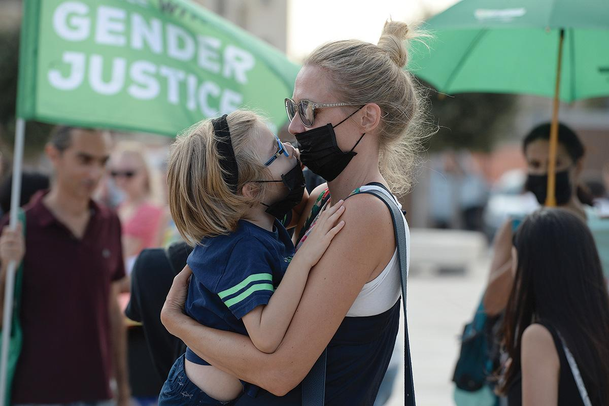 A mother and daughter kiss through masks during a climate change demonstration in Valletta on September 20. Photo: Matthew Mirabelli