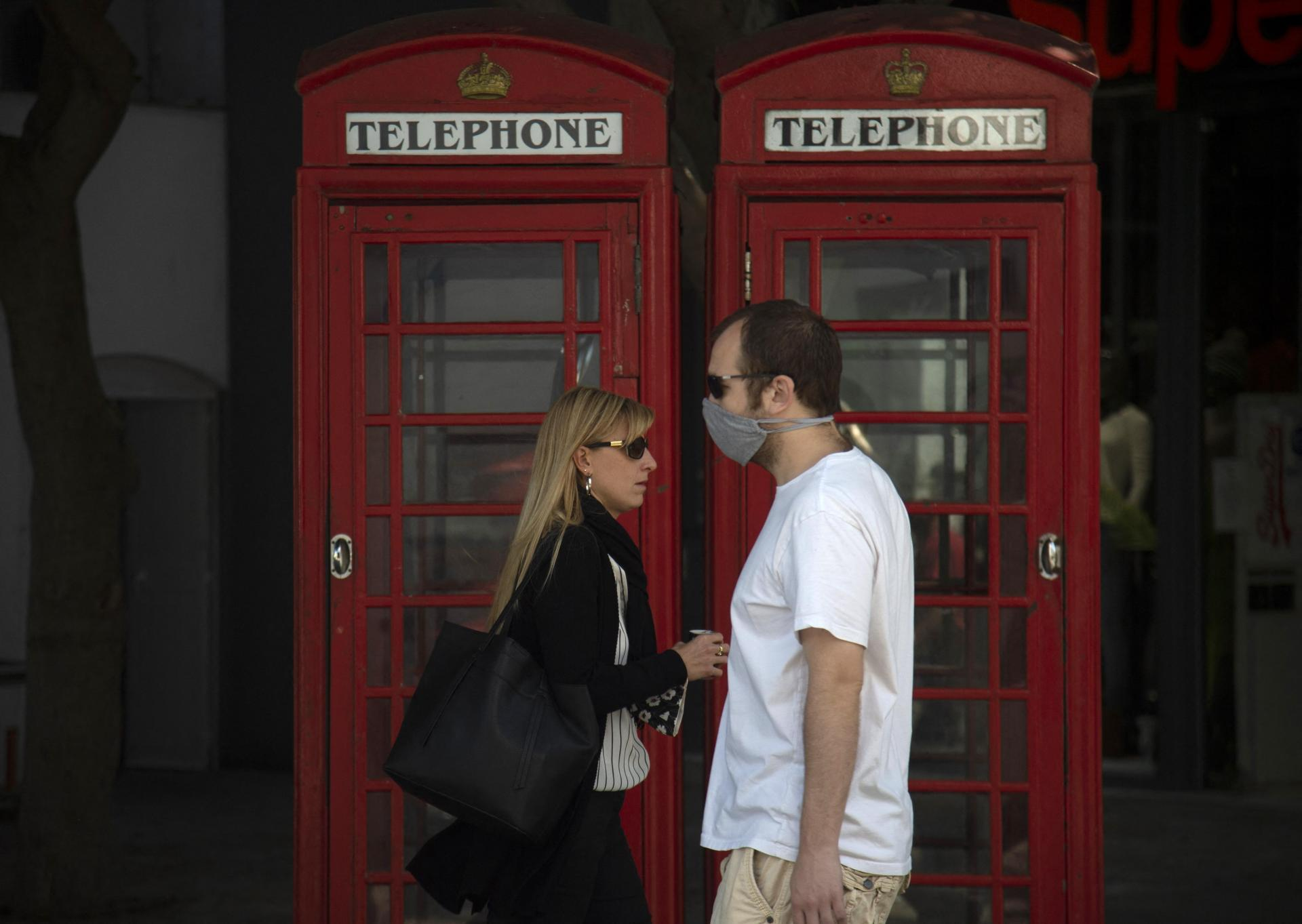 Two people walk past red telephone boxes in Gibraltar.