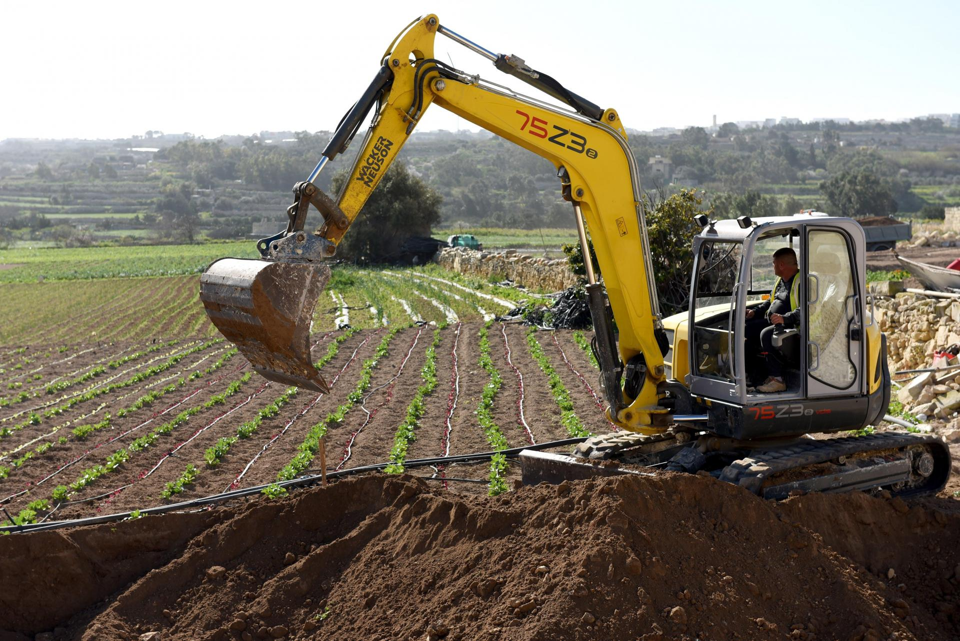 An excavator digs up farmland to make way for a wider road. Photo: Chris Sant Fournier
