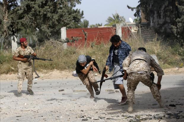 Libyan fighters loyal to the Government of National Accord (GNA) run as they fire their guns during clashes with forces loyal to strongman Khalifa Haftar.