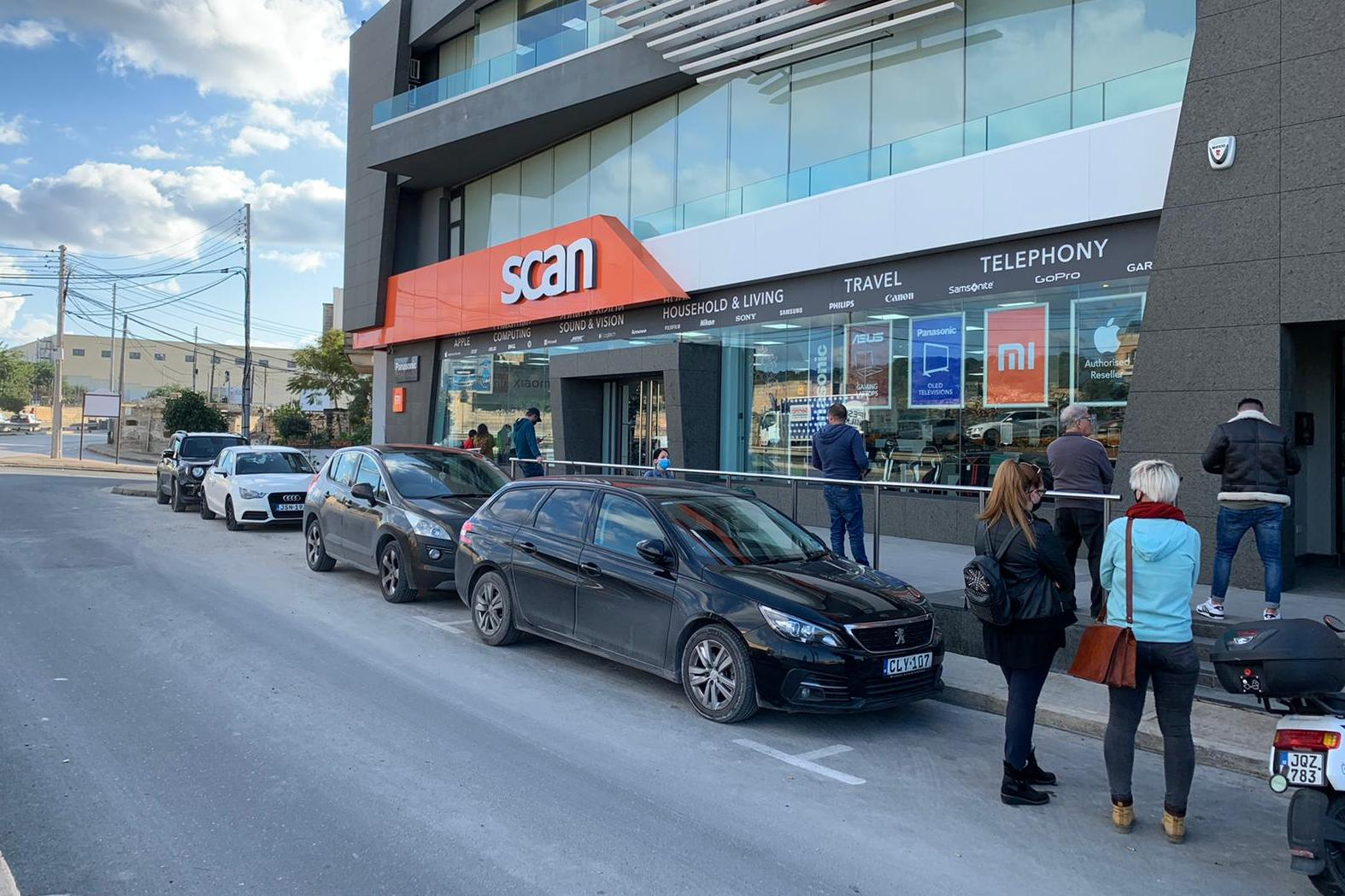 A handful of people queued outside Scan, where last year customers queued for two hours before the store opened. Photo: Jessica Arena