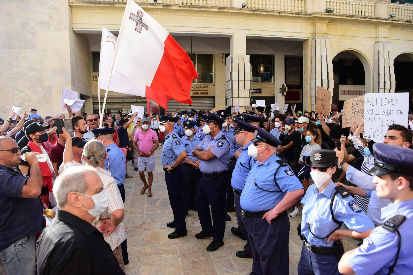 Police officers keep a close eye on anti-immigration protesters. Photo: Mark Zammit Cordina