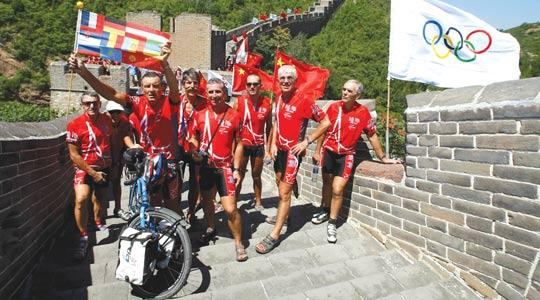 Cyclists hold up flags after arriving at the Great Wall ahead of the Beijing Games yesterday. The 101 cyclists left Paris in March and travelled through 12 countries, covering a total of 13,050 km.