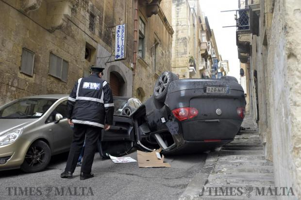 A police officer looks at a car after the driver lost control and flipped it three times. Photo: Mark Zammit Cordina