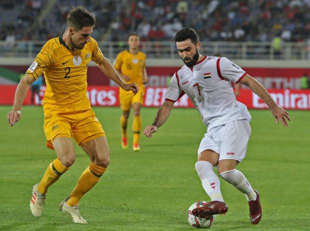 Australia's defender Milos Degenek (left) fights for the ball with Syria's forward Omar Khrbin.
