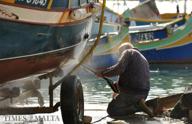 A man waterblasts the hull of his boat at Marsaxlokk on January 4. Photo: Chris Sant Fournier
