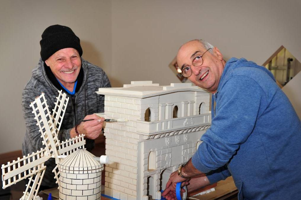 Volunteers painting the replica buildings in limestone colour. photograph: Ziggy Lewis