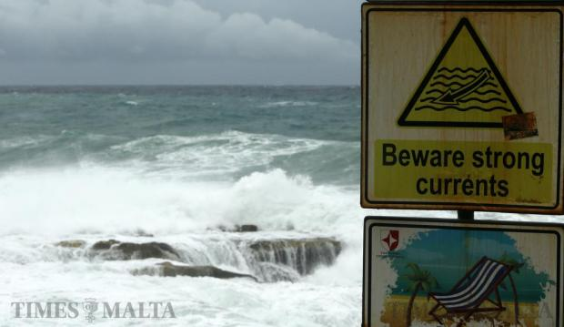 A sign warning of dangerous currents is seen as waves crash ashore at Fond Ghadir in Sliema on December 17. Photo: Darrin Zammit Lupi
