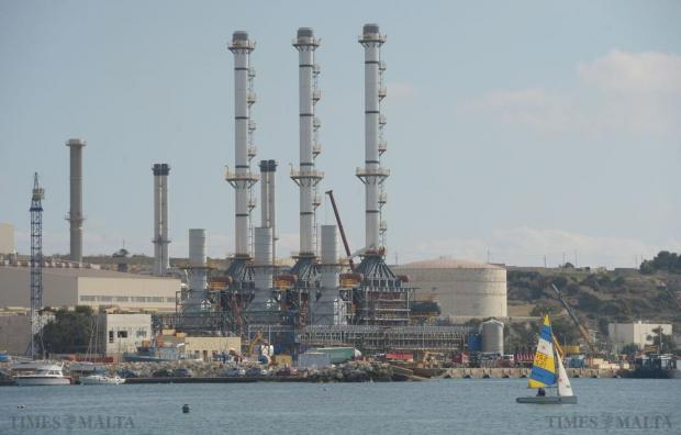 Works to convert the power station in Delimara to gas take shape as a dinghy sails past in Marsaxlokk Bay on December 19. Photo: Matthew Mirabelli