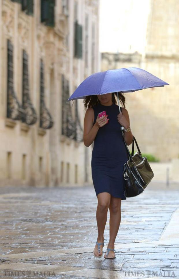 A lady walks down Merchant street with her umbrella after a brief rainstorm in Valletta on August 25. Photo: Matthew Mirabelli