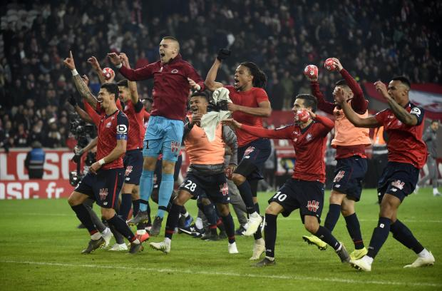 Lille's players celebrate after winning.