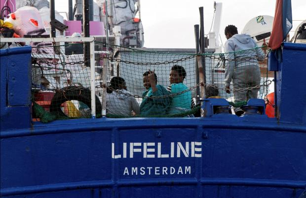 Migrants are seen on the deck of Mission Lifeline rescue boat in the central Mediterranean Sea.