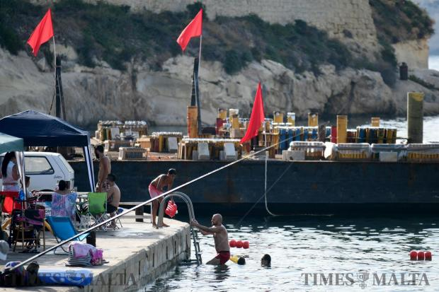 Bathers swim in the shadow of a fireworks barge berthed in Rinella Bay on August 6 Photo : Jonathan Borg