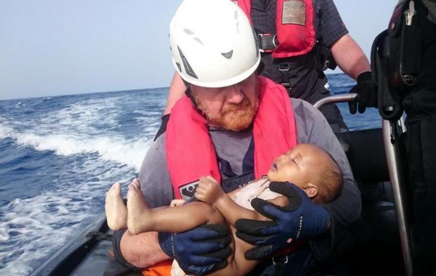 Martin Kolek holding a dead migrant baby in 2016.