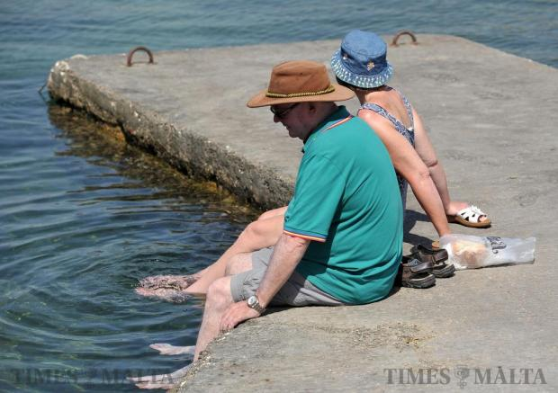Tourists dangle their feet in the sea in an attempt to cool down at Bugibba on July 13. Photo: Chris Sant Fournier