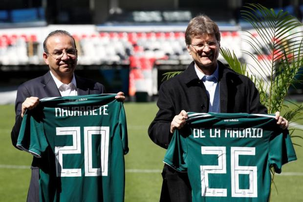 Alfonso Navarrete Prida, Interior Minister, and Enrique de la Madrid, Secretary of Tourism, gesture with their jerseys during the presentation of the government guarantee for the tri-nation North American bid to host the 2026 World Cup at Azteca stadium in Mexico City.