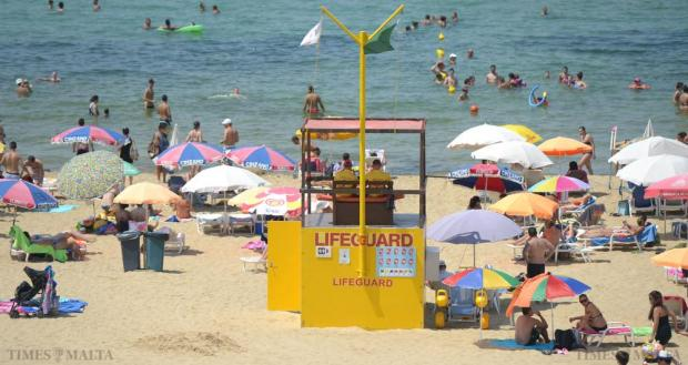 Lifeguards keep watch as people descend on Golden Bay on August 10 as the whole island slows down during the Santa Marija week. Photo: Matthew Mirabelli