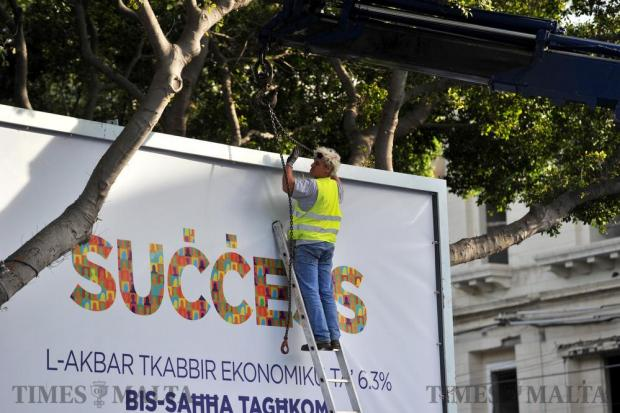 A worker removes a political billboard in Msida on June 3, after the Planning Authority ordered irregular billboards must be removed. Photo: Steve Zammit Lupi