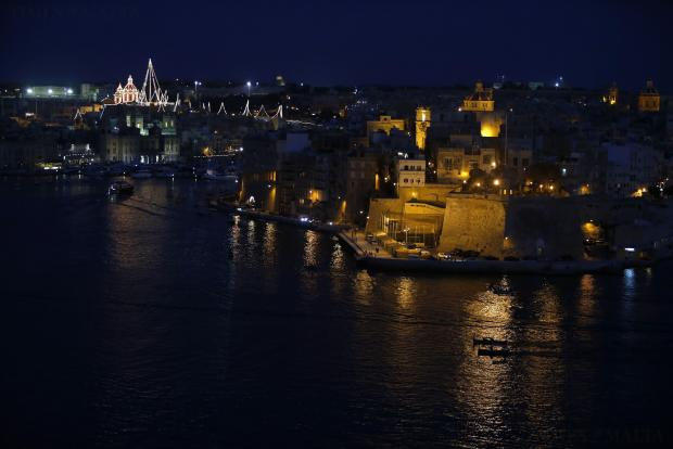 Oarsmen row their traditional racing boat (bottom R) past the fortified city of Senglea while training for the Victory Day regatta races taking place on September 8, at dusk in Valletta's Grand Harbour on August 22. Photo: Darrin Zammit Lupi