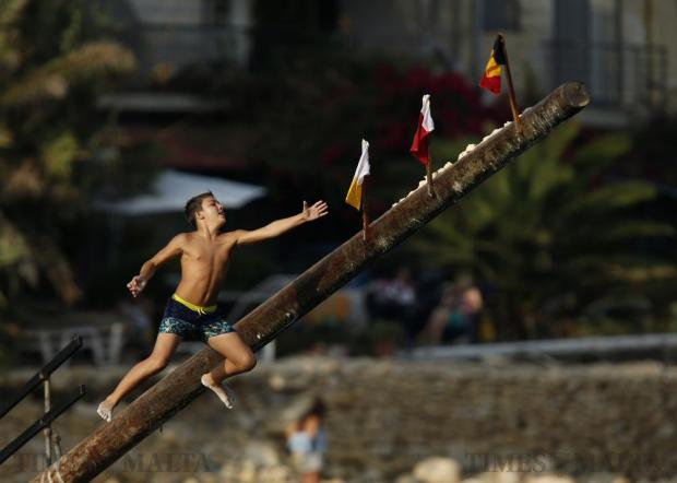 """A child tries to grab a flag on the """"gostra"""", a pole covered in grease, during the religious feast of St Julian, patron of the town of St Julian's, on August 27. In the traditional """"gostra"""", a game stretching back to the Middle Ages, young men, women and children have to make their way to the top and try to uproot one of the flags to win prizes. Photo: Darrin Zammit Lupi"""