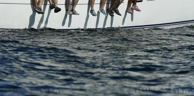 Crew members' feet hang over the side of a sailing boat at the start of the Rolex Middle Sea Race in Valletta's Grand Harbour on October 22. Photo: Darrin Zammit Lupi
