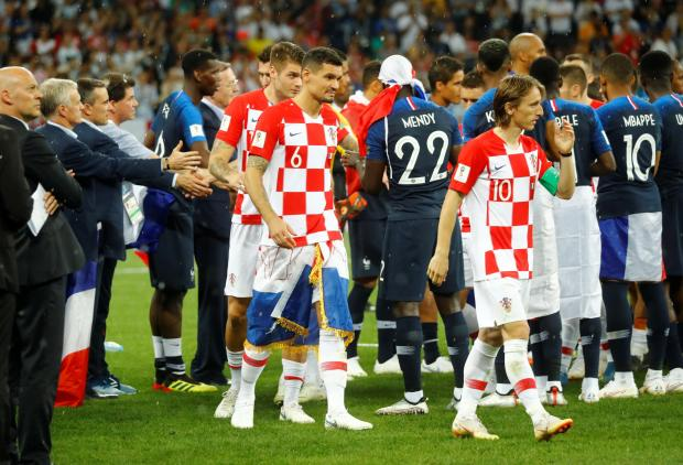 Croatia players shake hands with France players as they walk to receive silver medals.