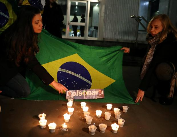 People light candles and hold up a Brazilian flag in solidarity with Mr Bolsonaro. Photo: Reuters