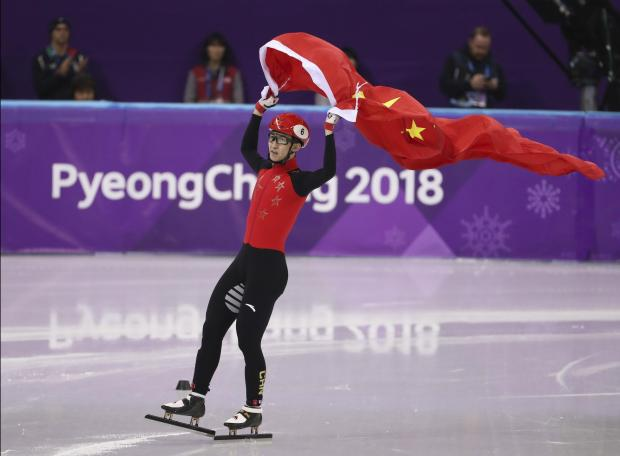 Gold medallist Wu Dajing of China celebrates with his national flag.