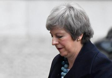 May is savaged at home after delaying Brexit vote