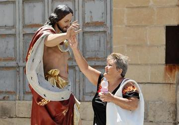 A woman touches the hand of a statue of Christ the King in Paola. Photo: Chris Sant Fournier