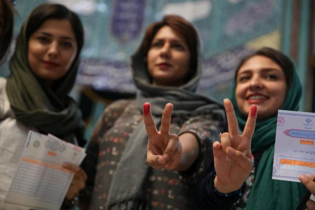 Iranian women show their ink-stained fingers after casting their votes. Photo: TIMA via Reuters