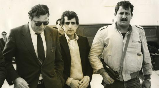 Omar Mohammed Ali Rezaq (centre) accompanied by armed security guards and his lawyer Joseph Mifsud during an on-site inquiry in his trial.