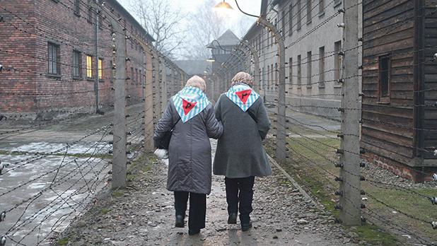 Two women walk along a path surrounded by barbed wire in the Auschwitz concentration camp. Photo: Daniel Schäfer/dpa-Zentralbild/dpa Picture-Alliance