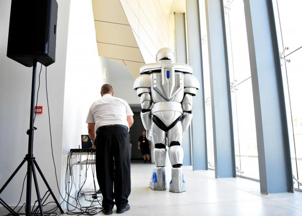 A large robot walks past a man at the Esplora science center in Kalkara on July 10. Photo: Mark Zammit Cordina
