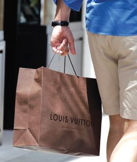A man with a shopping bag from the luxury brand Louis Vuitton in Beverly Hills, California.