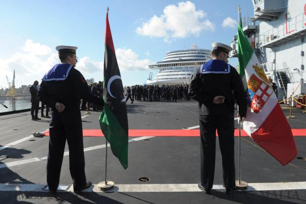 Italian sailors hold flags during a ceremony in which 89 members of the Libyan coast guard were presented with certificates. The ceremony took place on board the Italian training vessel San Giorgio in Valletta, Malta on February 8.