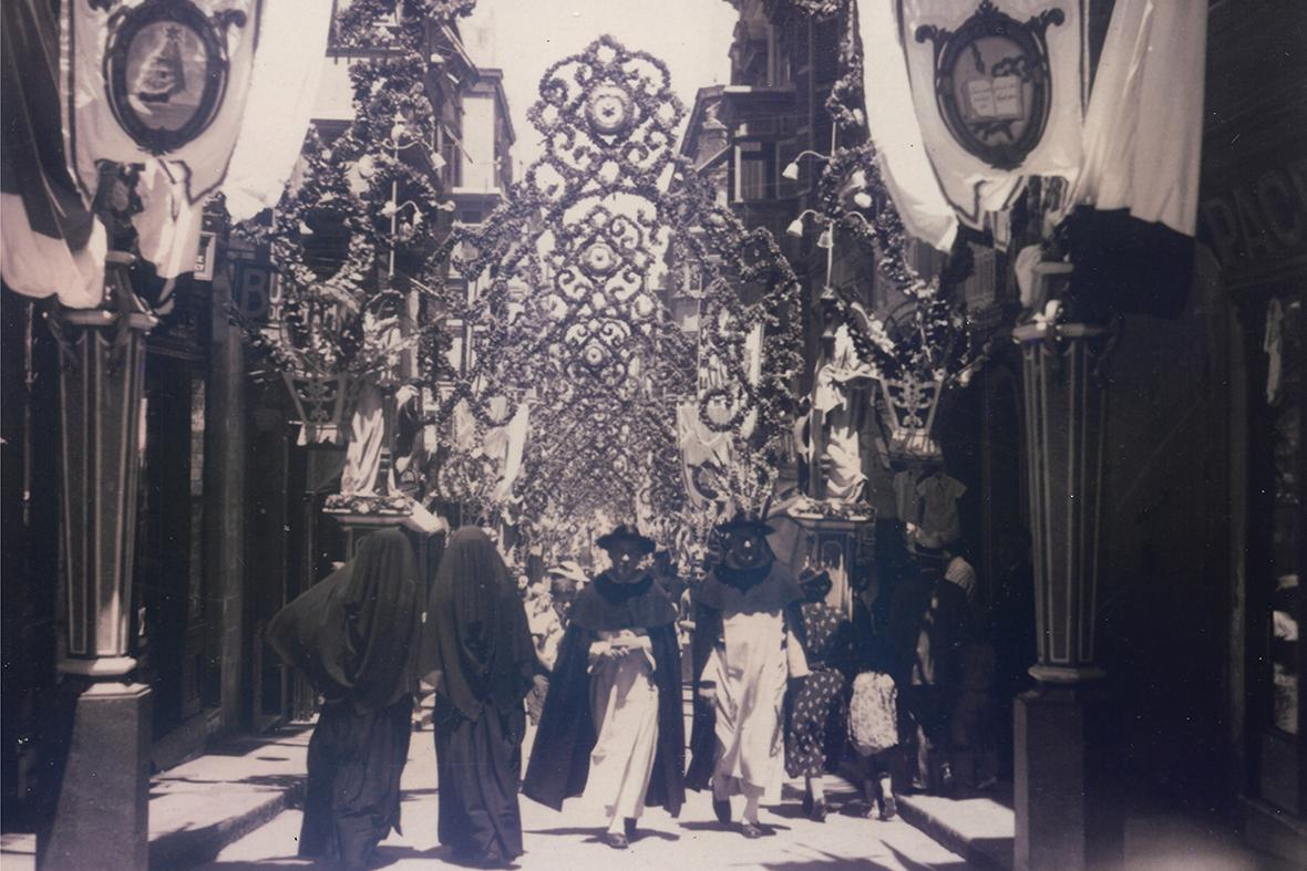 Locals walking underneath the paper decorations in Old Theatre Street, Valletta, in 1923.