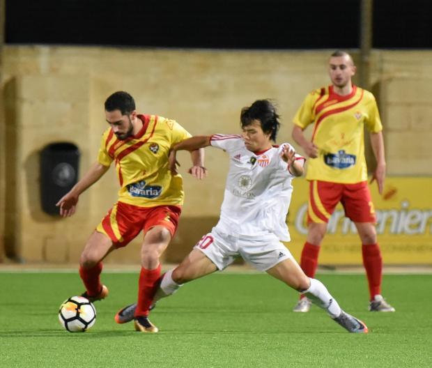 Hubert Vella of Senglea Athletic shields the ball from Lija Athletic's Kei Hirose. Photo: Mark Zammit Cordina