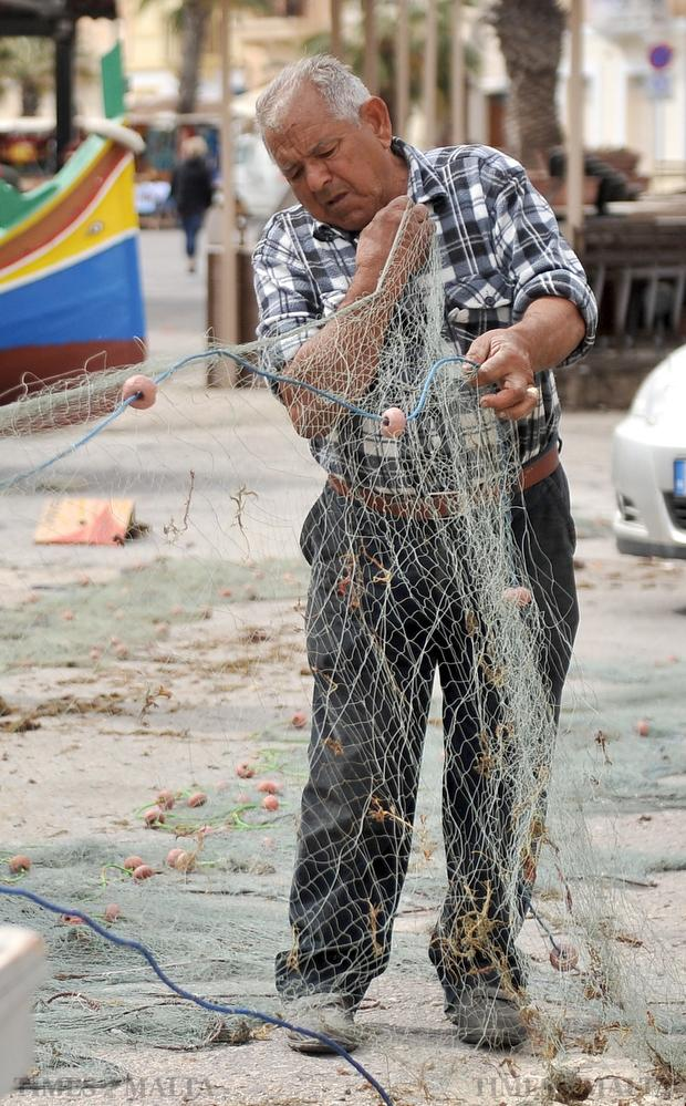 A fisherman untangles his net at Marsaxlokk on February 29. Photo: Chris Sant Fournier