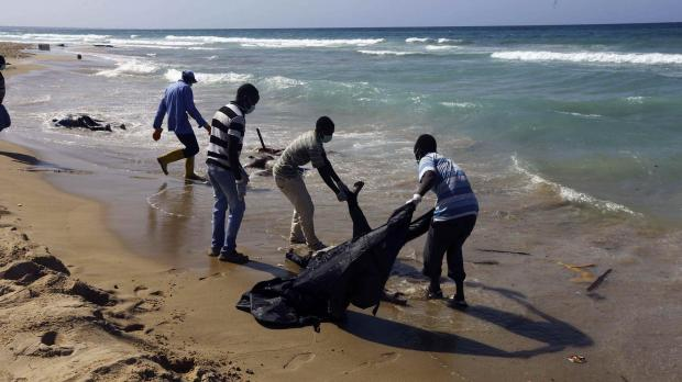 File photo - workers bag bodies of migrants that drowned off Tripoli's coast last month.