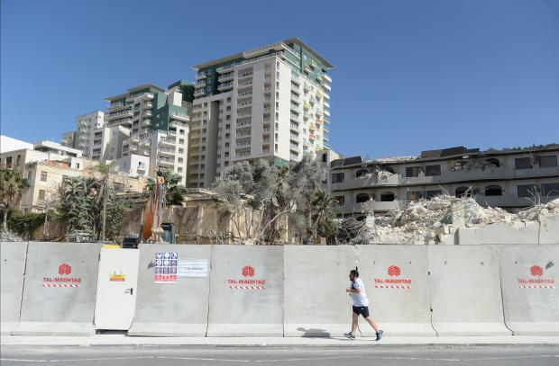 A jogger runs past concrete blocks covering the site where the Fortina Hotel stood in Tigne on March 11. Photo: Matthew Mirabelli